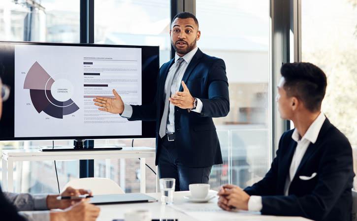Un jeune homme d'affaires donne une présentation à ses collègues dans la salle de conférence d'un bureau d'allure moderne.
