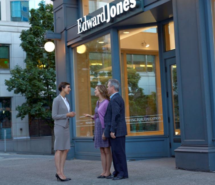 Un représentant en services financiers et un couple, à l'extérieur d'un bureau d'Edward Jones.