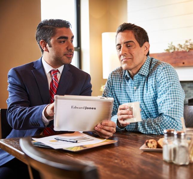 Un représentant en services financiers tient une tablette tout en discutant avec un homme.'