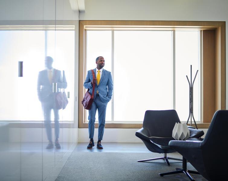 Un homme en complet se tient le long d'un mur de verre réfléchissant.