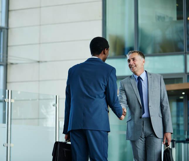 Deux hommes d'affaires se serrent la main dans le hall d'un immeuble de bureaux.