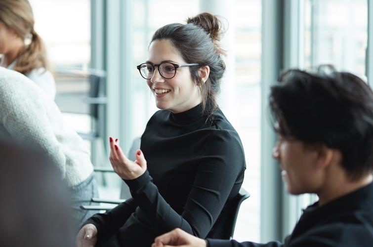 Une femme assise à une table de conférence est en pleine discussion.