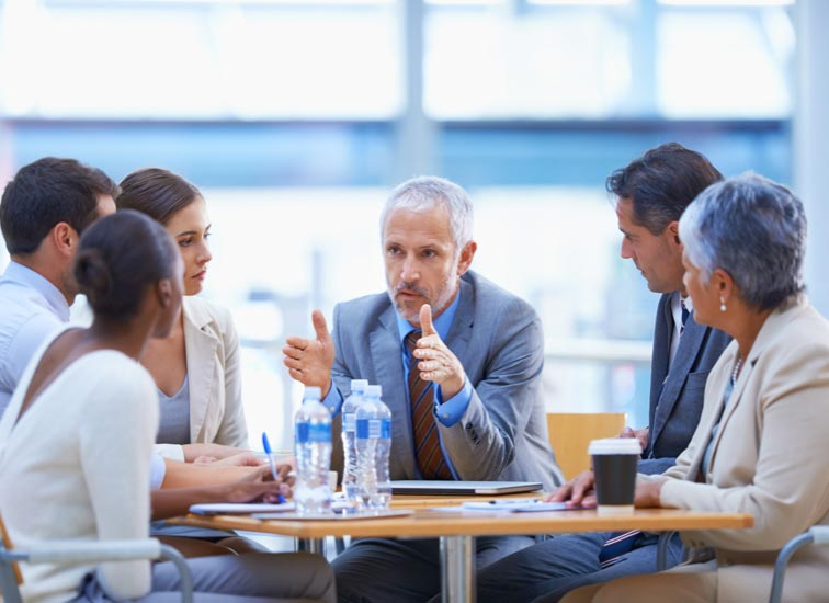 Un homme parle à un petit groupe de professionnels.