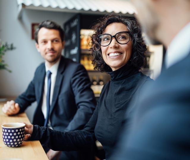 Une femme et un homme souriants, assis à une table, discutent avec un autre homme.