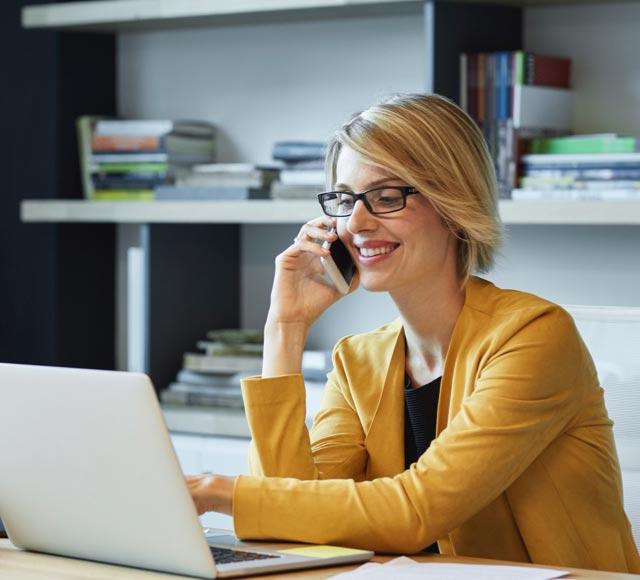 Une femme parle au téléphone et tape sur un ordinateur portable.