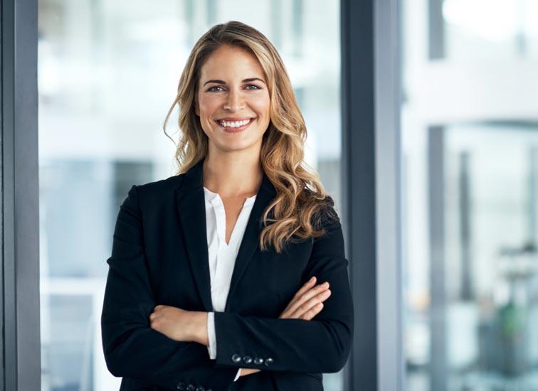 Une femme d'affaires souriante, les bras croisés.