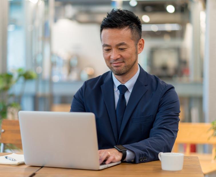 Un homme tape sur un ordinateur portable.