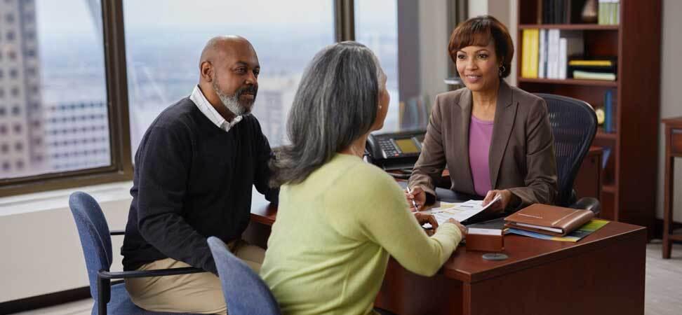 Un couple d'aînés assis au bureau d'une représentante en services financiers.
