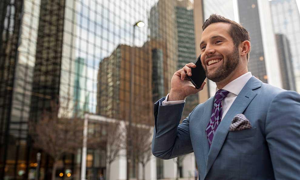 Business man talks on cell phone on city sidewalk
