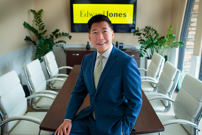 Man in suit sitting on conference room table