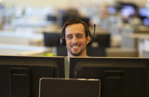Men smiling at his computer monitor while wearing an audio headset