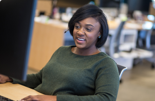 Woman smiling and sitting at a desk in an office