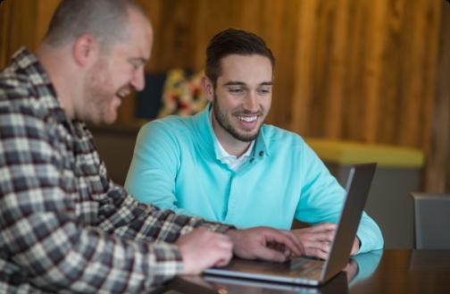 2 men working at a laptop