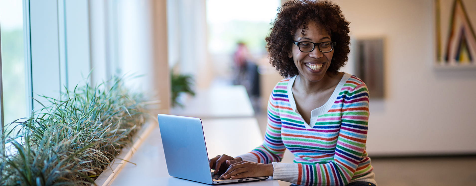 Woman smiling while sitting at her laptop