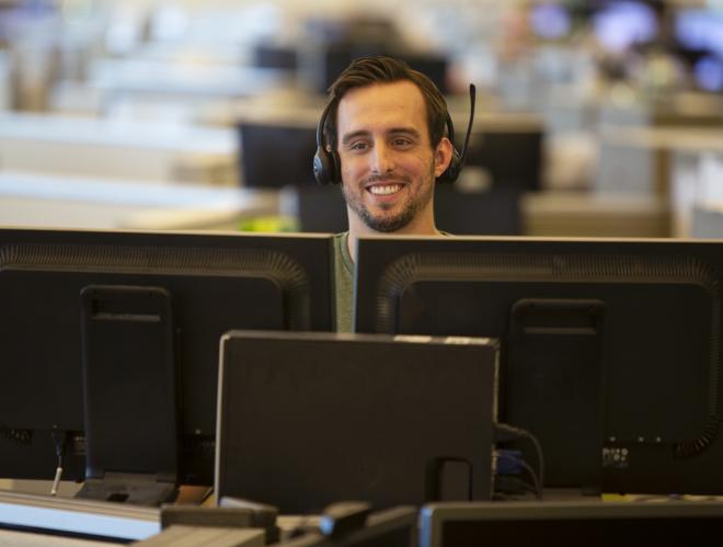 Man smiling behind multiple monitors
