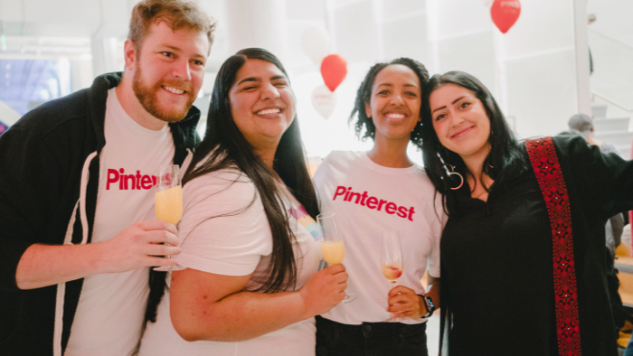 Group of Pinterest employees, smiling and holding champagne glasses