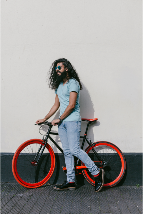 Man with long hair posing with a red bike next to a wall.