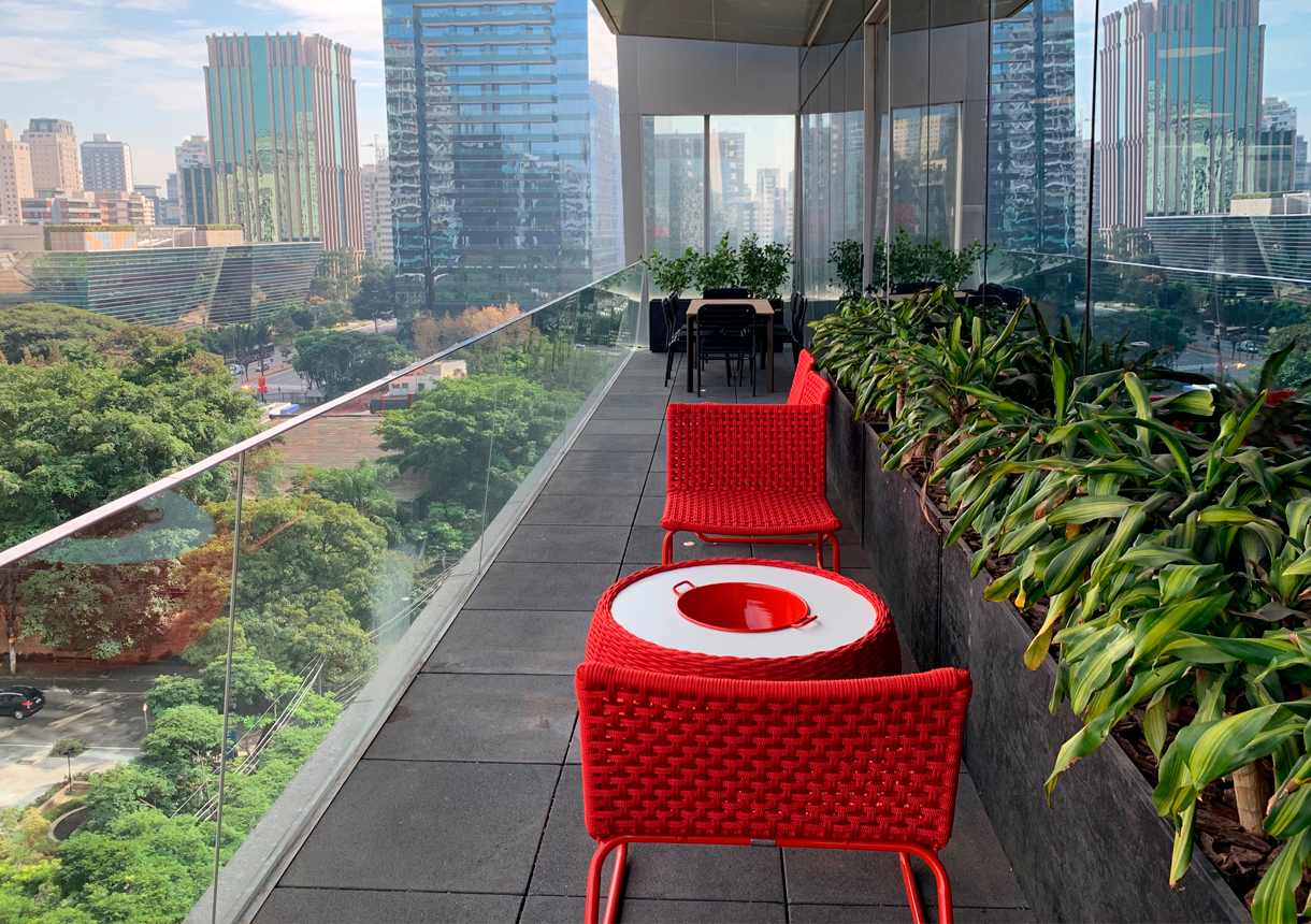 A lush office patio with furniture overlooking a neighborhood in the city.