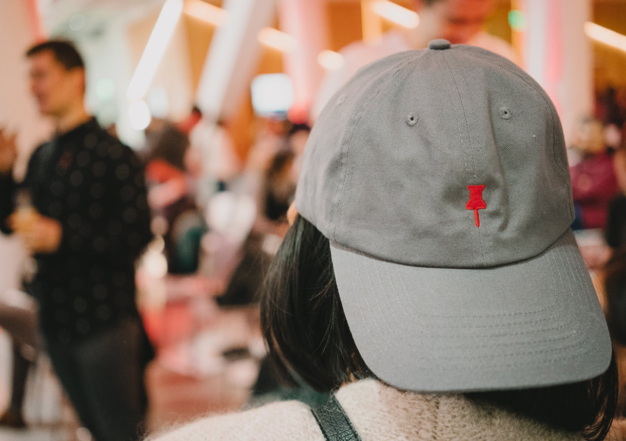 View of conference attendee from behind wearing a grey hat.