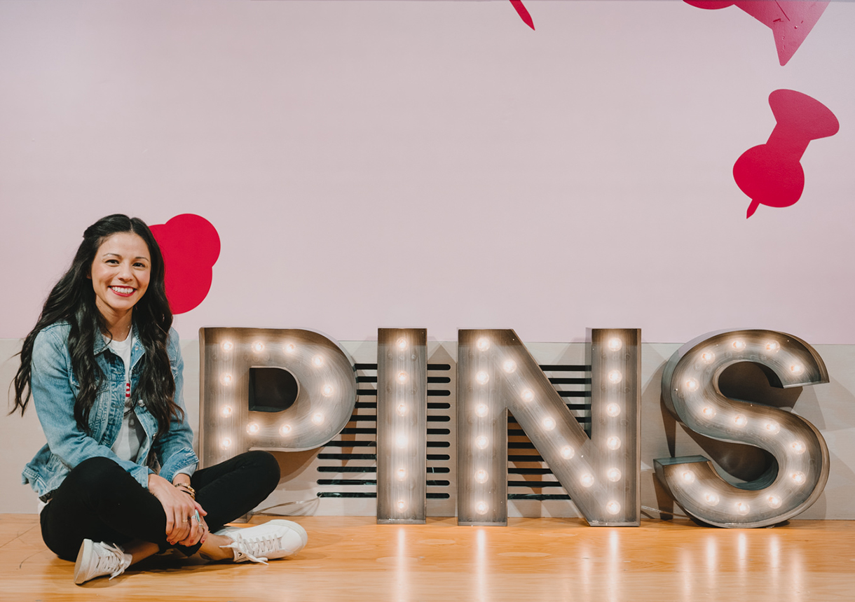 Decorative light letters that spell PINS with a woman sitting on the floor next to them.