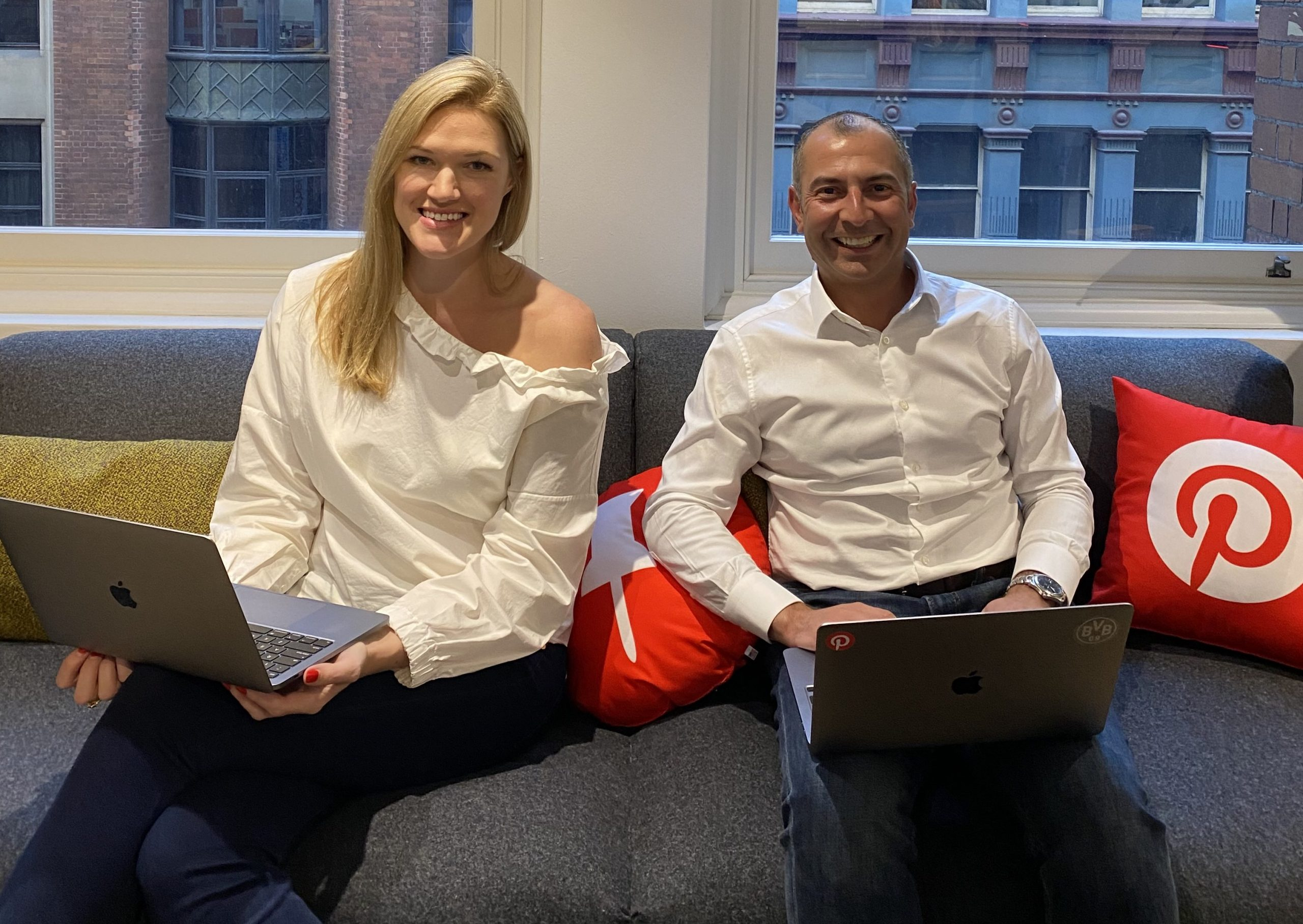 Lottie Laws and Sam Christou on a couch with a Pinterest throw pillow