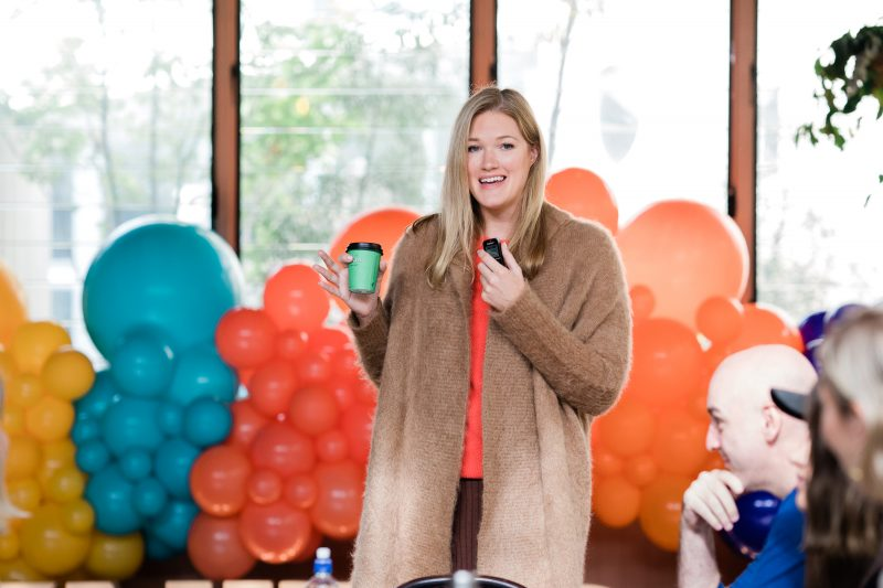 Pinterest's Lottie Laws in front of decorative balloons at Knit Con 2021