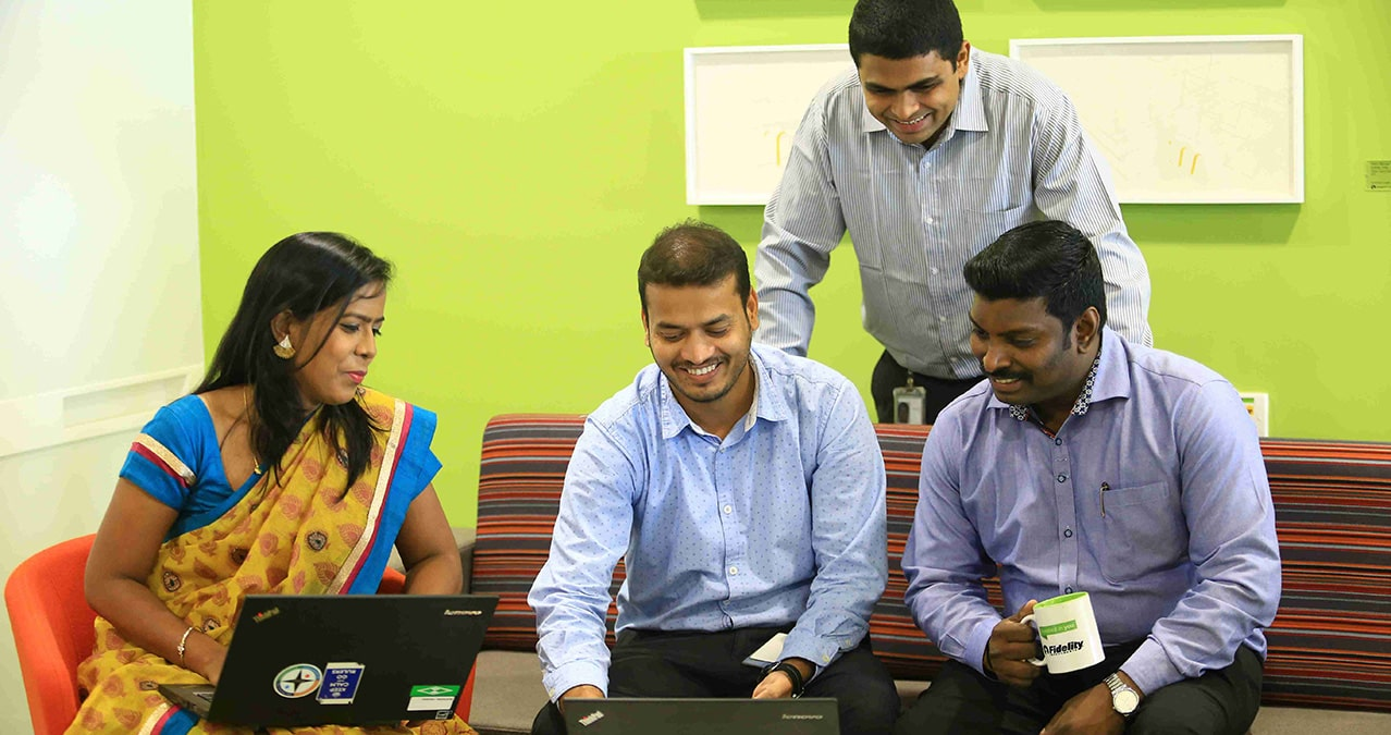 Four employees gathered around laptop while working