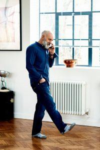 Man wearing socks walking around the house on the phone.