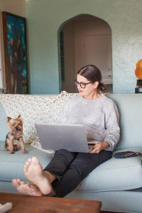 Woman with her feet up on the coffee table working from home.