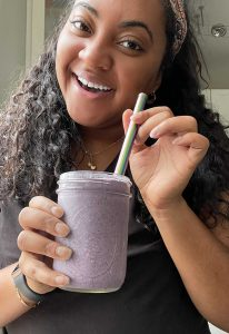 A woman showing the camera her smoothie creation.