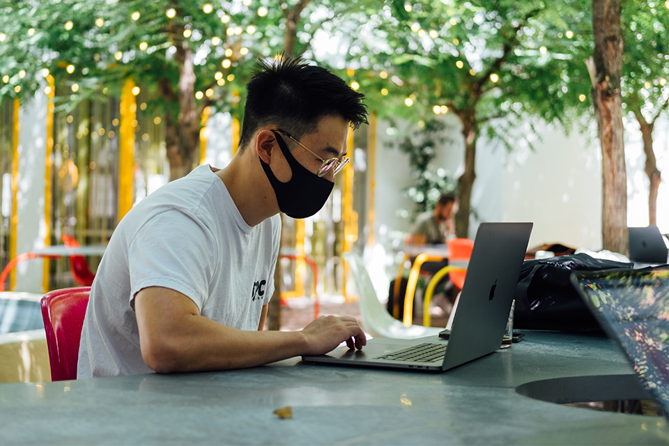 Man in mask working in a public space outside.