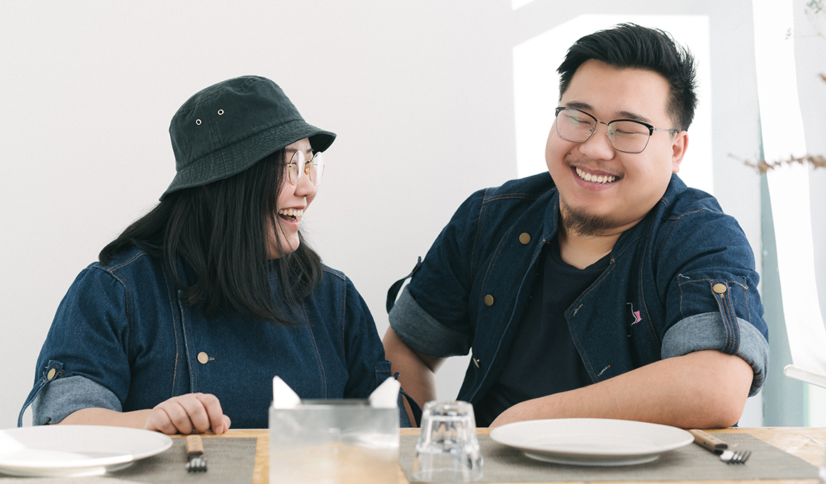 Shot of man and woman sitting together and laughing.
