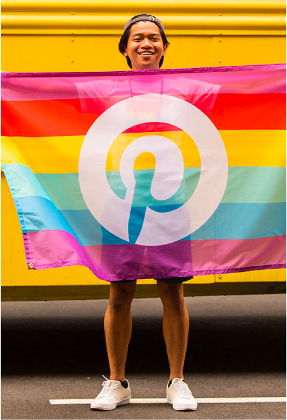 Man holding up a Pinterest flag with the Pride colors.