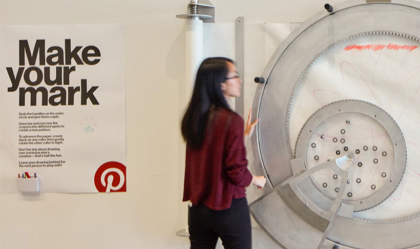 Woman standing in front of an extra large spirograph and a poster on the wall reads, Make Your Mark.