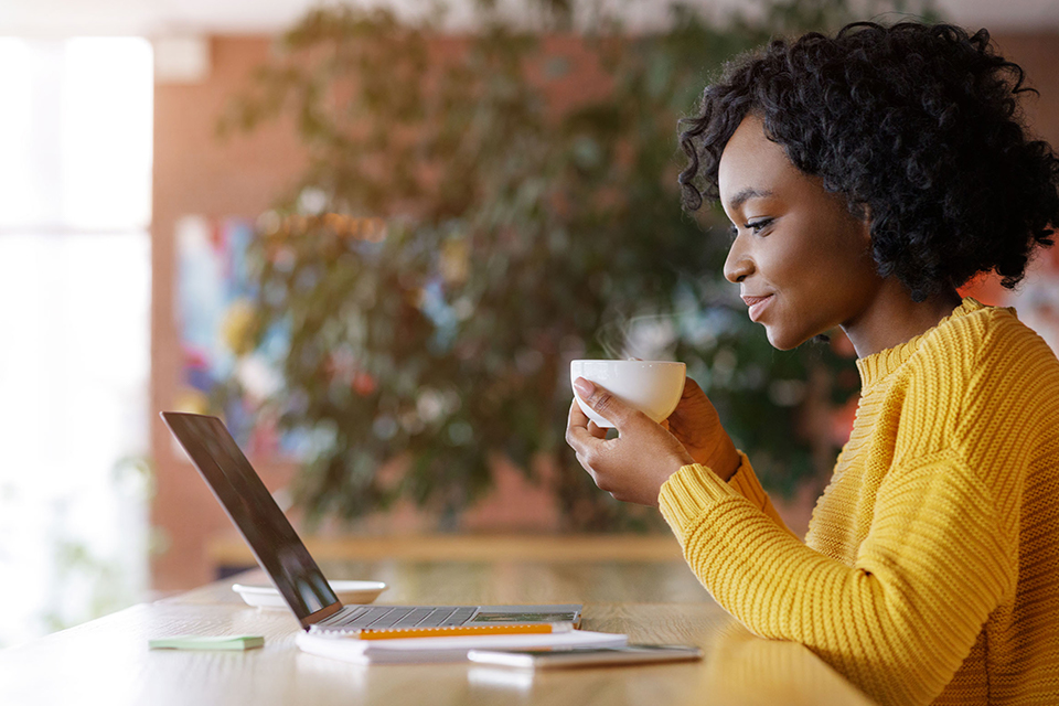 Woman sipping from a coffee cup while smiling and looking at her laptop