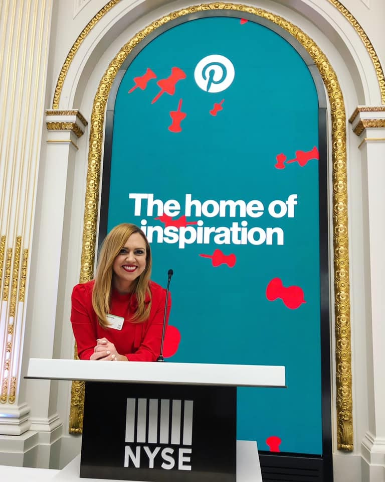 Erin Elofson in front of a banner that reads, The home of inspiration