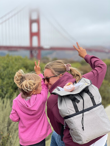 Pinployee Julene and her daughter in front of the Golden Gate Bridge, wearing a Pinterest backpack