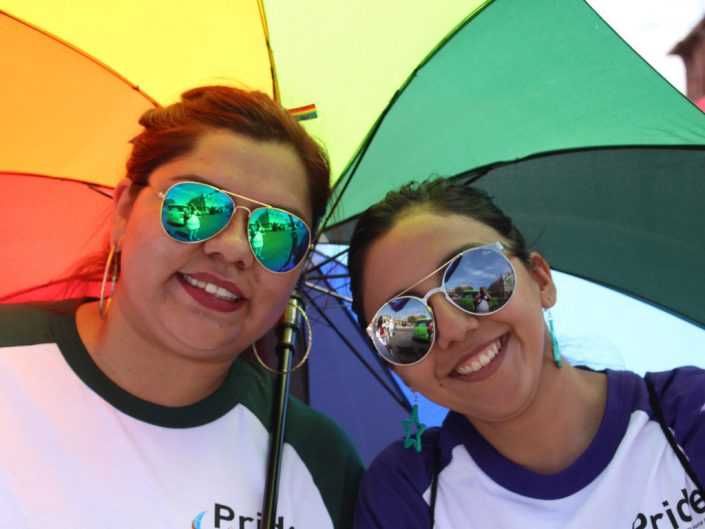 Two sunglass-wearing ADP associates smile for the camera, while holding a rainbow-colored umbrella above their heads.