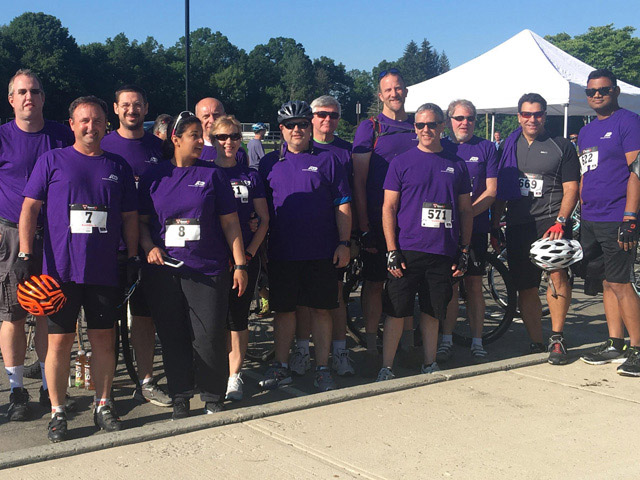 Group of ADP associates in purple t-shirts and cycling gear who participated in Pedal for Preservation in New Jersey.