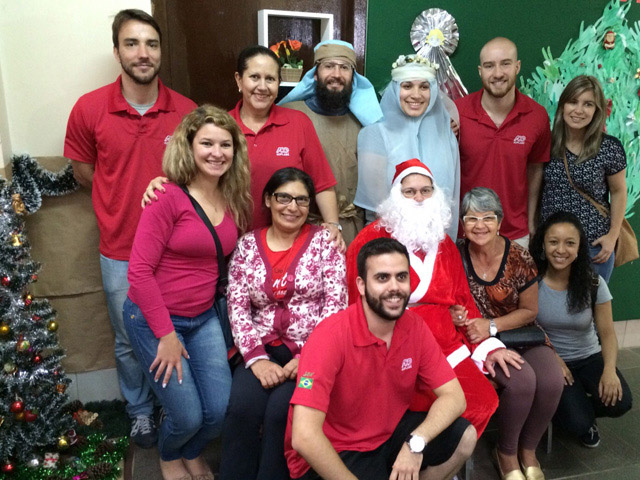 Christmas holiday picture of a group of ADP associates in Brazil wearing red shirts and standing around three others dressed as Mary, Joseph and Santa Claus.