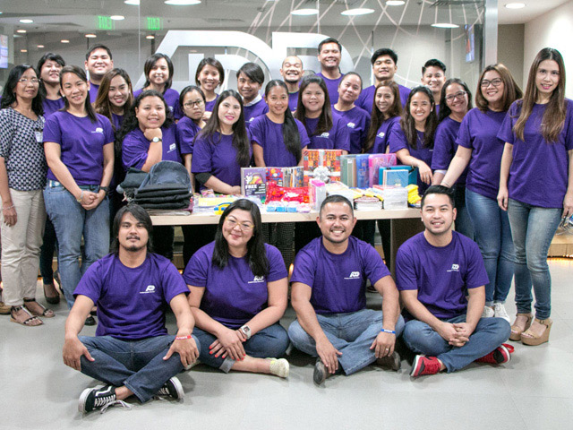 Group of ADP associates in purple t-shirts that participated in the Back to School program in the Philippines.