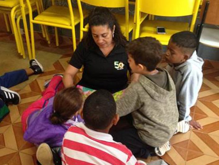 An ADP associate, who volunteered for the Read to Children program in Brazil, is surrounded by, and reading to, four young children.
