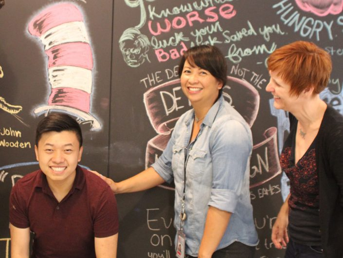 Three ADP employees smiling and having fun in front of an illustrated wall