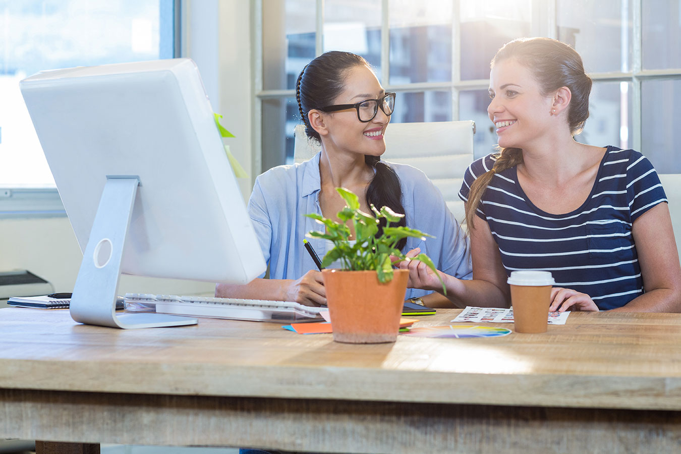 Two female associates collaborating together at work