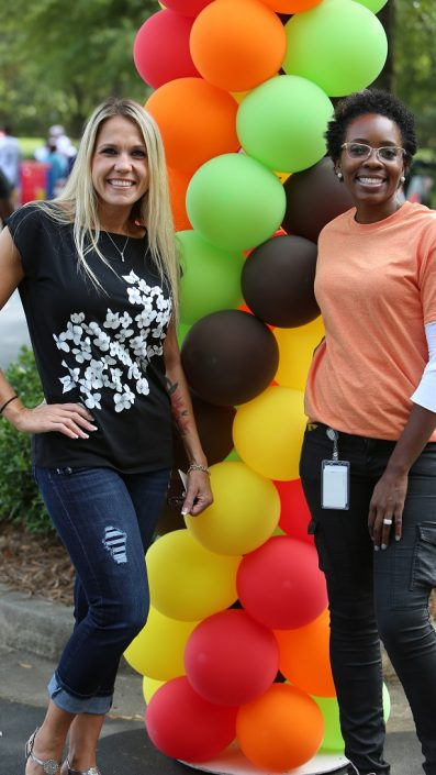 Two smiling women standing with balloons at Fall-A-Palooza event.