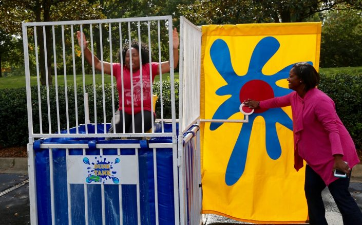 Woman inside a dunk tank and another woman hitting the release bar.