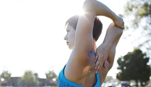 athletic woman with arms over-head and stretching