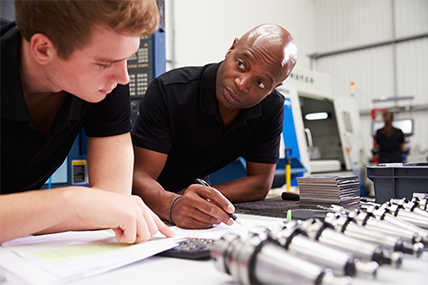 engineer and apprentice looking over papers behind cylindrical metal parts