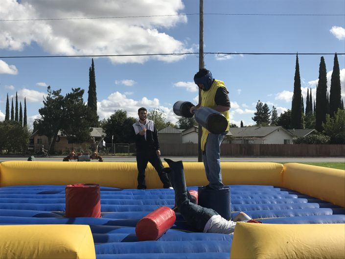 Foster Farms employees on inflatable playing surface, one employee fallen down and the other holding cushioned paddles