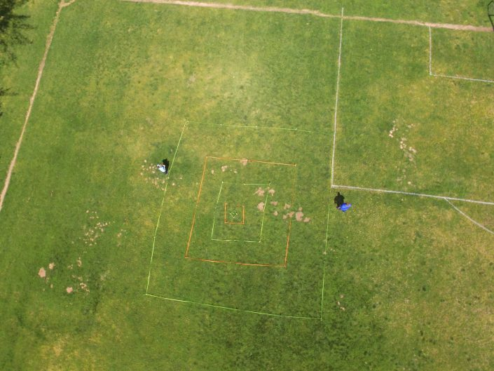 Overhead view of grassy field with concentric squares marked in orange & green